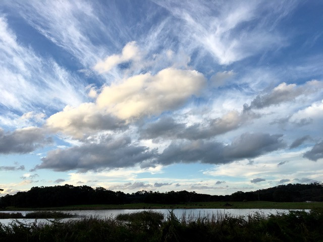 Streaky, puffy, white and dark clouds aove a lake with low hills around it.