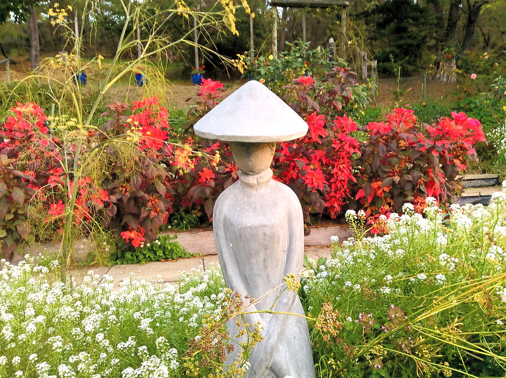 Grey statue of hatted woman in garden with red and white flowers.