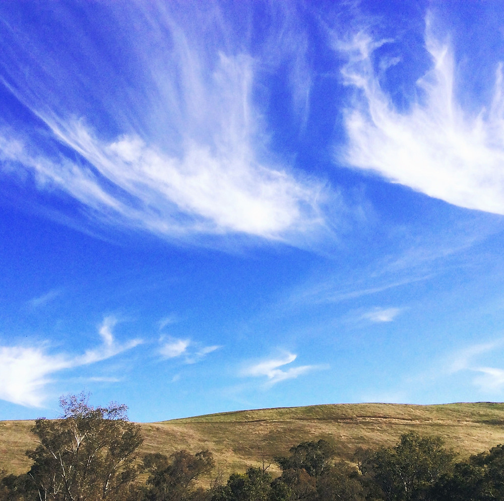 Fine clouds reaching upwards above gently rolling hills.