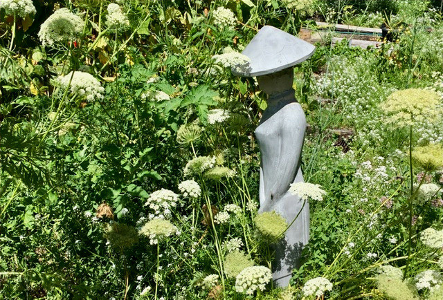 Simple grey statue in a garden, of a woman