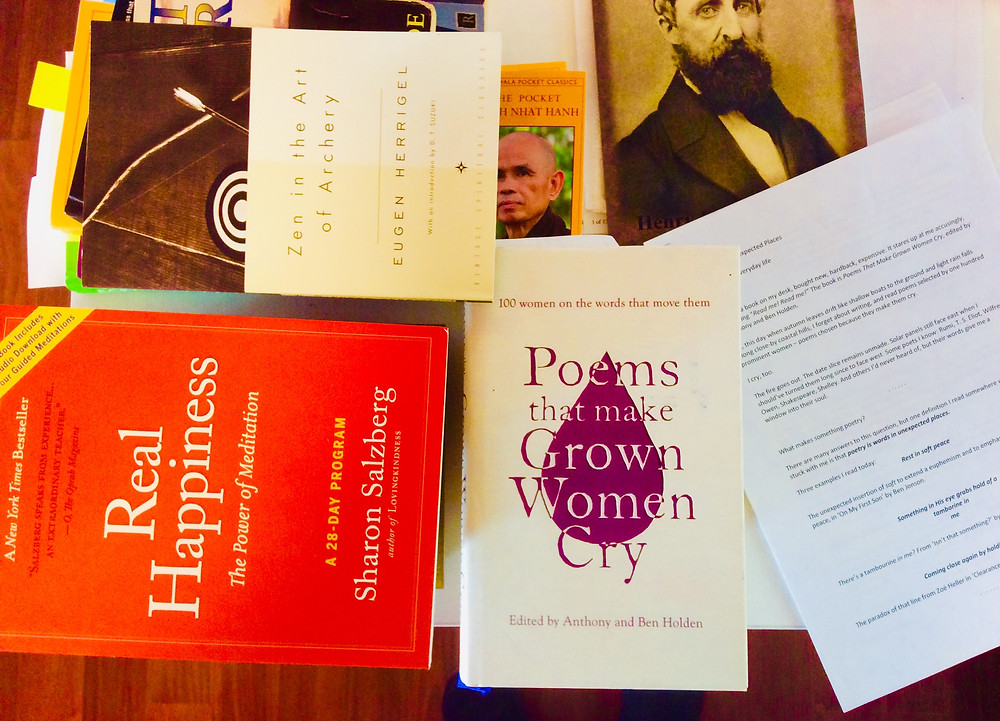 Colllection of books face-up scattered on desk.