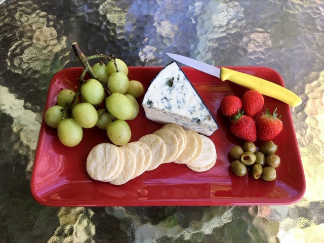 Red platter with grapes, blue cheese, strawberries, olives and crackers.