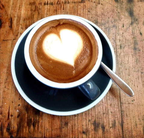 Cup of coffee with heart featured in the froth.