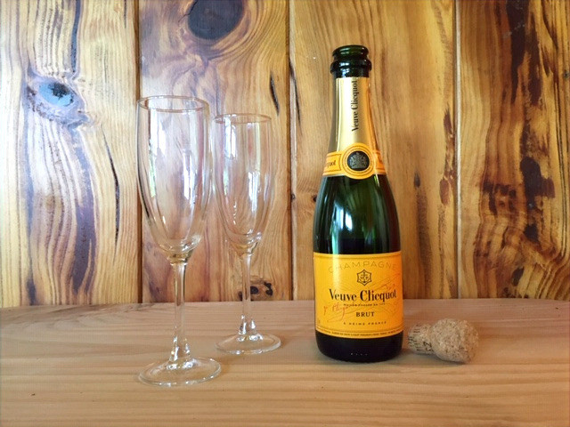 Small bottle of Veuve Clicquot with two champagne glasses, on wooden table.