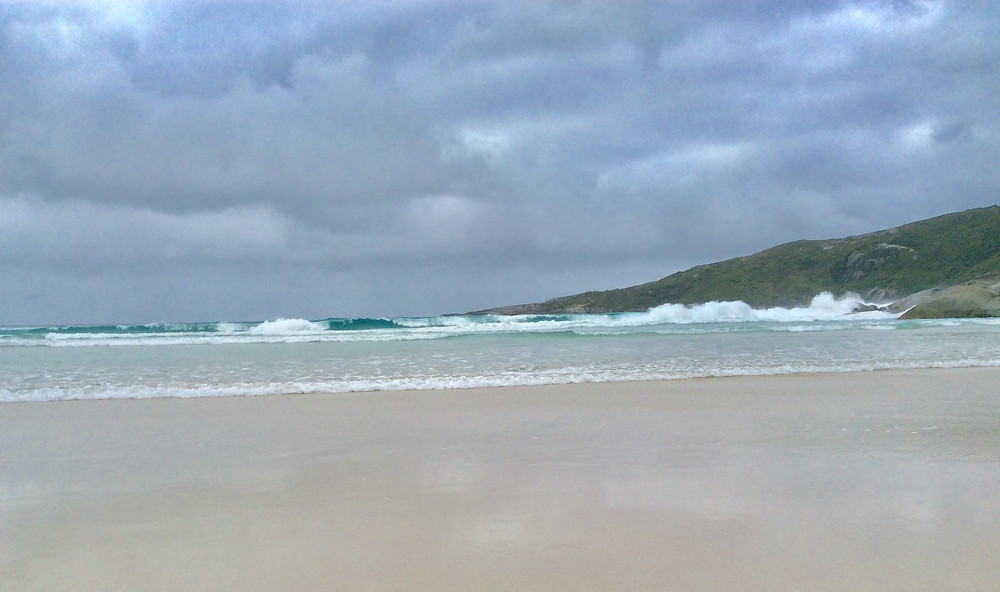 Beach scene with low waves, grey clouds and gentle green hill on the right