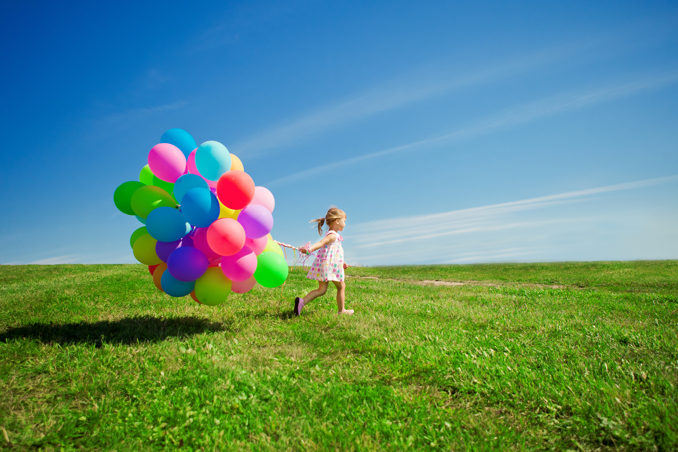Happy little girl holding colorful balloons. Child playing on a green meadow. Sm