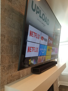 65 inch TV mounted to stone tile above f