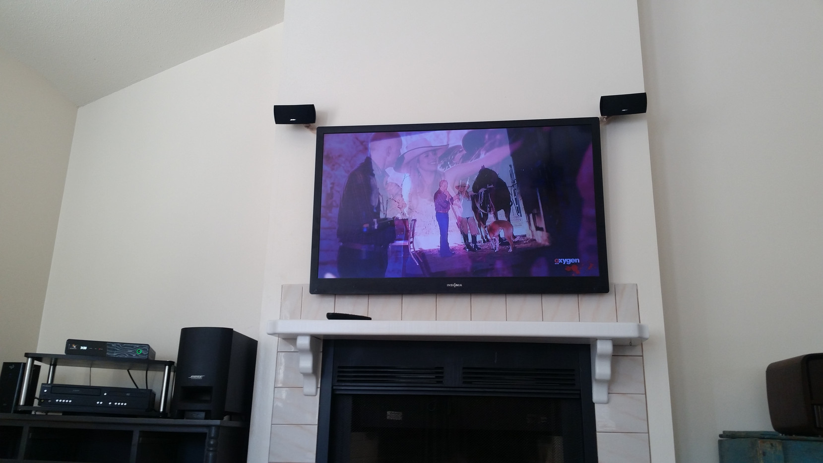 Navarre TV mounted above fireplace with speakers