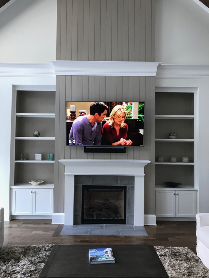 Destin FL TV mounted above fireplace with soundbar