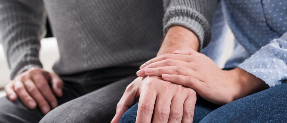 couple holding hands while in counsellin