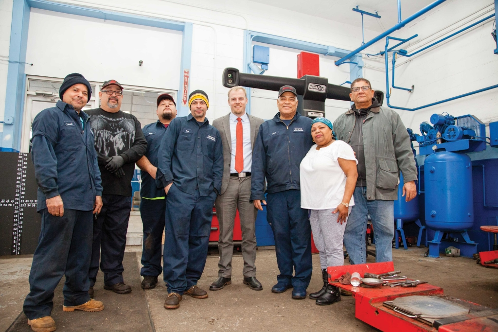 Jose Rosario, third from right, with his employees at Universal Auto Repair and Derek Mitchell (in suit), executive director of the Lawrence Partnership.
