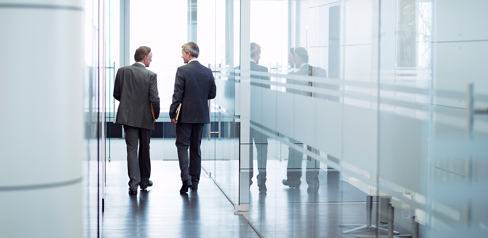 Two men walking in an office