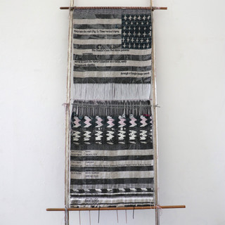 """Loom with Textile (After Charles Bell?), 2018  Loom with Textile (After Charles Bell?) interrogates the use of an 1875 photograph by Charles Bell, a photo which has been used and talked about in U.S. institutions and textile histories as a marker for U.S. patriotism and assimilation. In this photo, Juanita (Asdzáá Tl'ógí), a Navajo weaver and leader sits opposite U.S. Federal Agent Arny, and in between them is a weaving of a U.S. flag, zigzag """"eye-dazzler"""" stripes, and more horizontal stripes, all still tensioned on a loom. This weaving is titled Loom with Textile by the Smithsonian and is credited to Juanita (Asdzáá Tl'ógí)."""