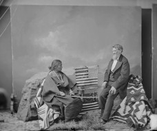 Photo by Charles M. Bell (?). Portrait of Juanita in Native Dress; Blankets, Weaving Implements and Governor Arny Nearby 1874. National Anthropological Archives, Smithsonian Institution. NAA INV 06396900.