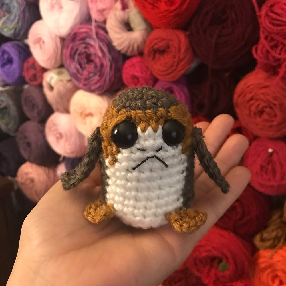 A hand is holding a small crocheted Star Wars Porg in front of a wall of yarn balls