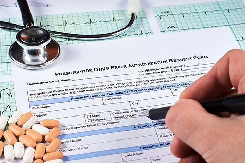 Human fill Prescription drugs prior authorization request form, pills, stethoscope on a EKG graph pa