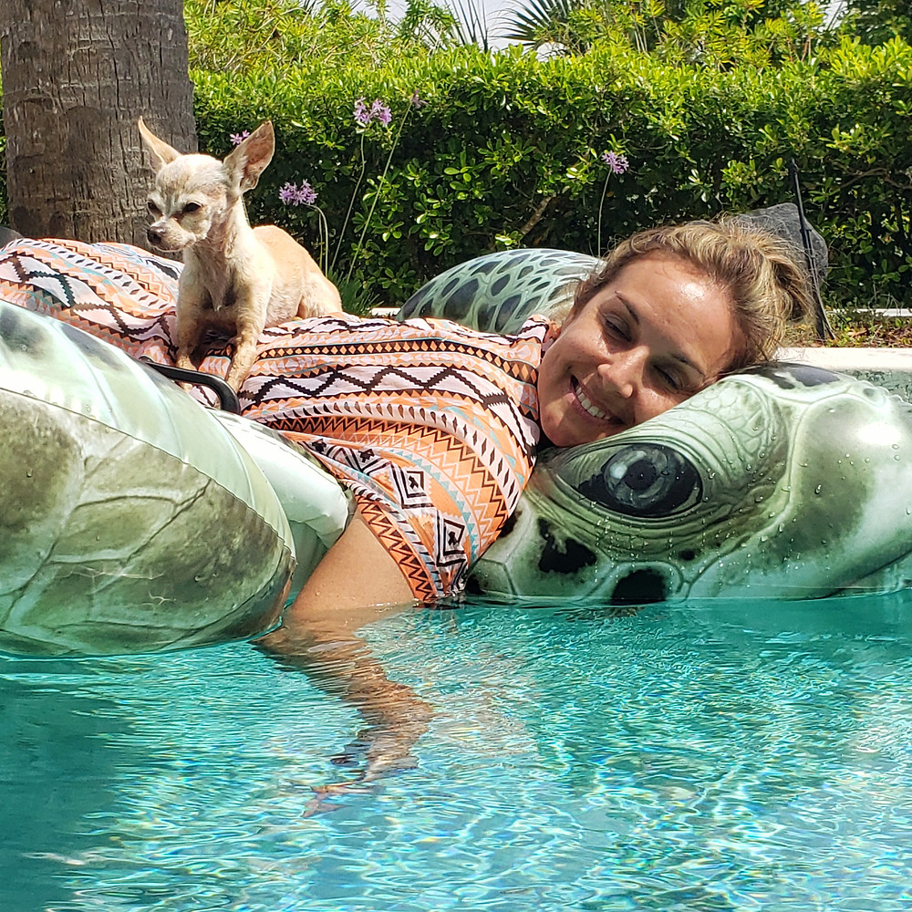 Traci's Paws spokesdog Emee the Chi and Traci's Paws Founder Traci Wilkerson Steckel floating in the pool.