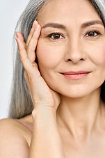 Vertical portrait of middle aged Asian woman's face with perfect skin. Older mature lady t