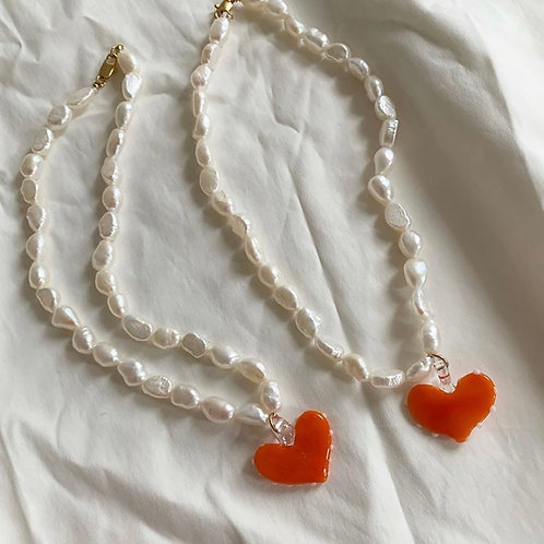 Orange heart on pearls