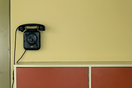 A photograph of a telephone above a storage unit.