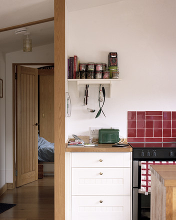 A photograph of a kitchenette with a bedroom in the background.