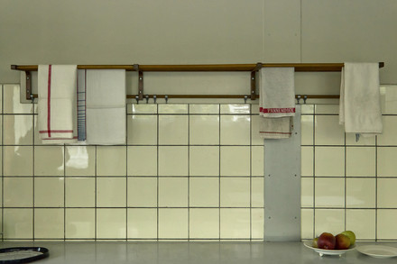 A photograph of a kitchen worktop with towels hanging above.