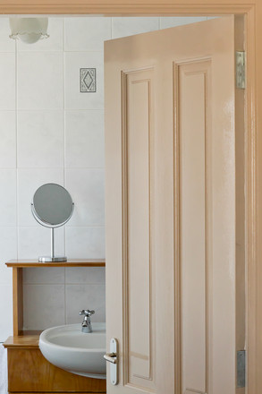 A photograph of a partly open doorwhich shows a sink.
