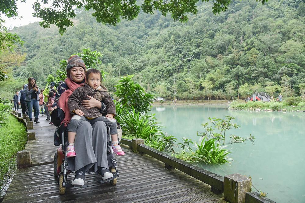 輪椅朋友與小朋友順著步道環遊湖邊。