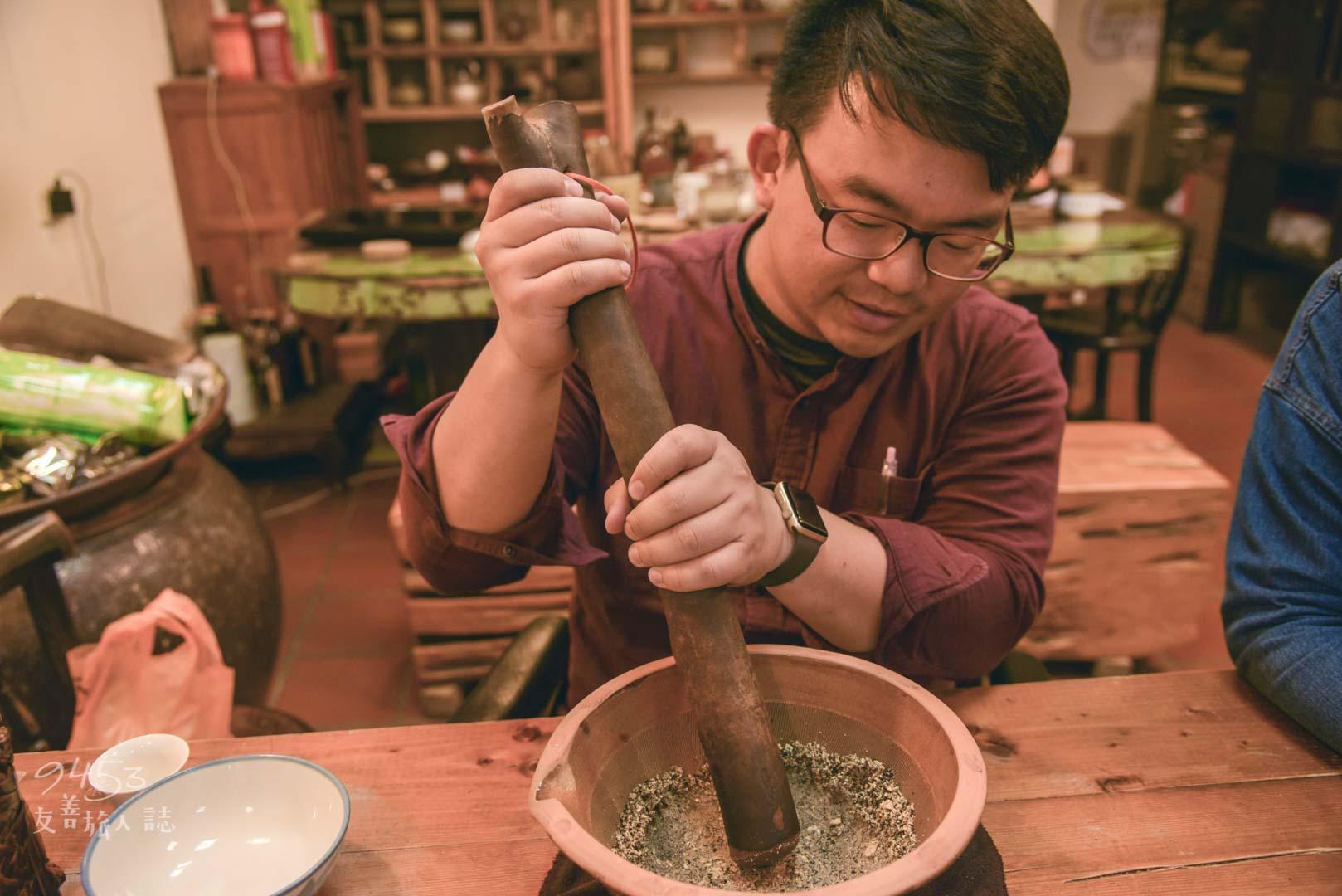 耐心將缽內的穀物與茶葉磨碎