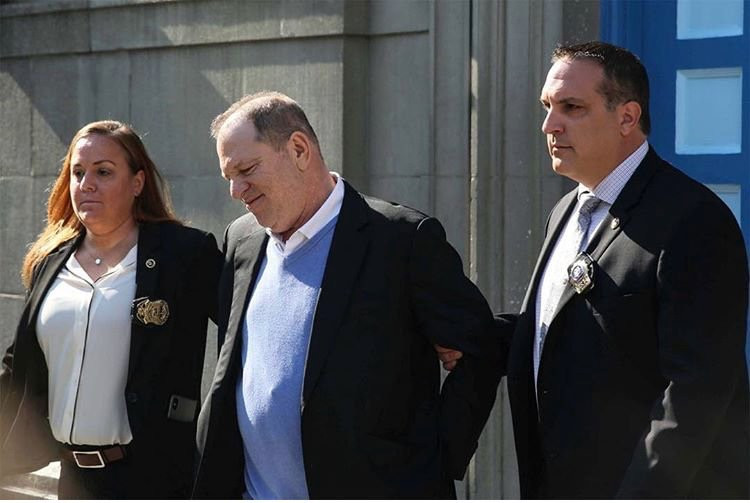 Disgraced media mogul and accused rapist Harvey Weinstein is led away in handcuffs as he surrenders to New York authorities