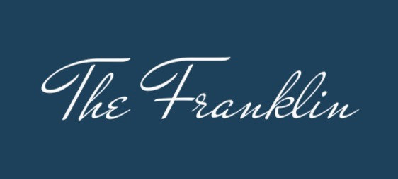 """""""The Franklin"""" in a stylized brush stroke script, used by the Franklin as their full name logo. The text is white and the image background is a dark teal."""