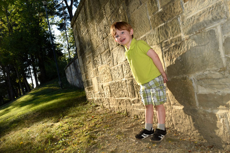 Young boy leaning on a wall