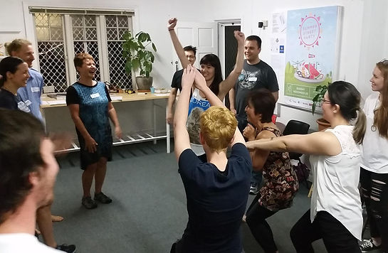 A group of people play an improv game. Four players are in the centre of the room striking poses, and the other people are watching and laughing with the players.