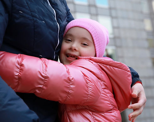 Girl with additional needs wearing a pink coat and smiling at the camera