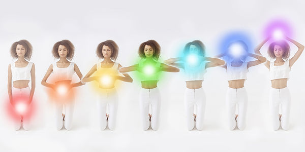 Woman meditating. Colored chakra lights over her body. Yoga, zen, Buddhism, recovery and w