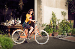 woman sitting on a bicycle in front of a thrift shop