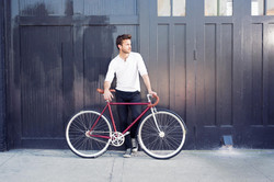 man holding a red fixie bicycle by a wooden gate