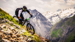 man riding a mountain bicycle down a hill