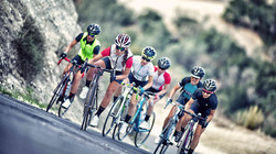 group of cyclist riding up a mountain hill