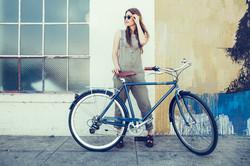 woman model posing behind a bicycle