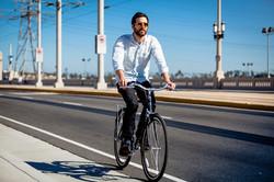 man riding a bicycle on a sidewalk