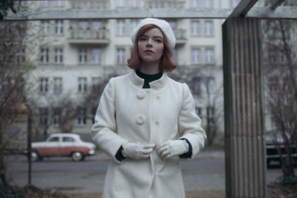 אישה במעיל וכובע לבן צועדת בשדרת קרל-מרקס בברלין