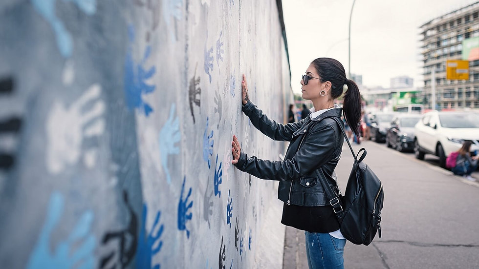 Young woman in front of Berlin Wall. (1)
