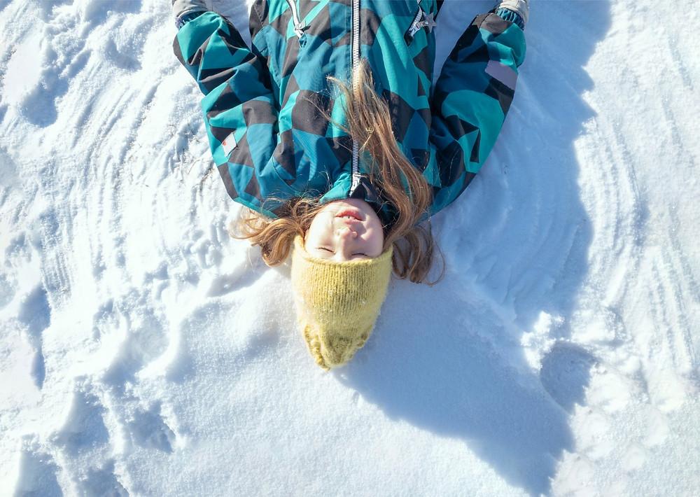ילדה שוכבת על השלג