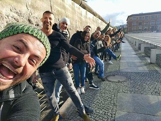 תיירים-מצטלמים-על-רקע-חומת-ברלין