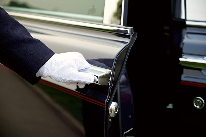 יד בכפפה לבנה פותחת דלת של רכב יוקרה