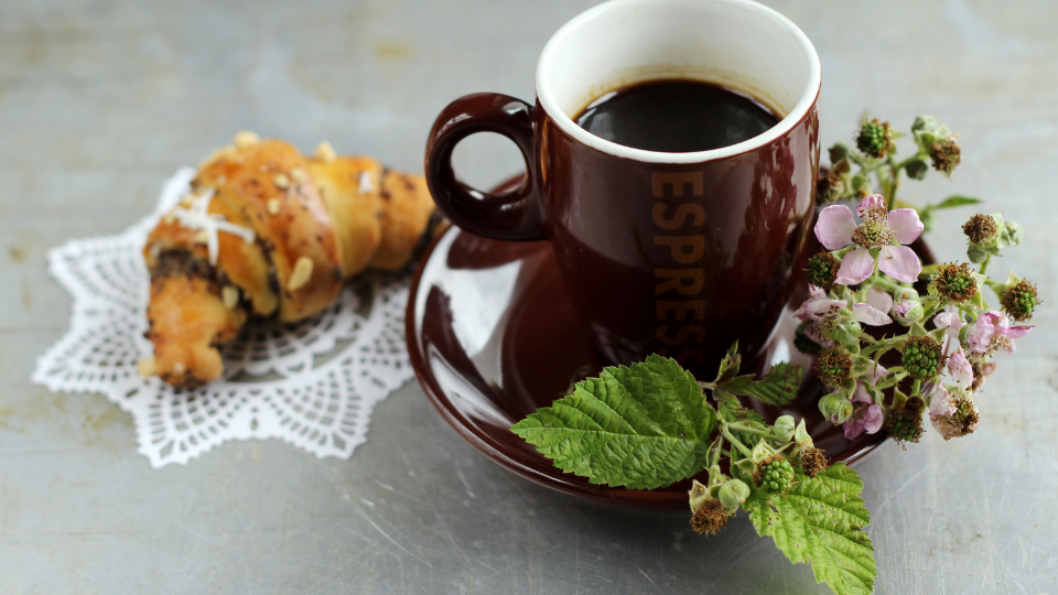 כוס קפה אספרסו לצד קרואסון שוקולד