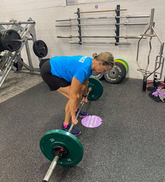 Lady dead lifting in a gym