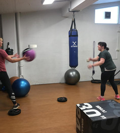 Two ladies throwing a fitness ball to each other in the gym