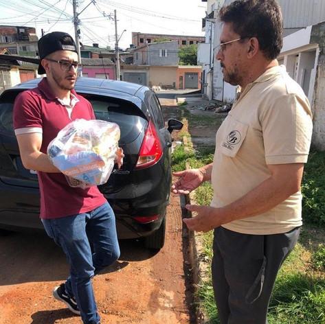 Voluntario Jean Carlos entregando a cesta basica